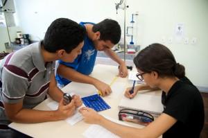 Estudantes trabalhando no laboratório de física experimental